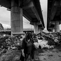 Stefano Schirato, Ida Pariante, 54 anni, cammina nel mezzo di una discarica illegale a Napoli. Sua figlia Martina è morta nel 2005 a causa di un nefroblastoma, quando aveva solo 9 anni., Napoli, 2015, dal libro Terra Mala. Living with Poison. © Stefano Schirato.