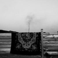 Stefano Schirato, Un tappeto appeso alla recinzione d'acciaio attorno al campo rom. In lontananza si alza una colonna di fumo nero, Masseria del Pozzo, Giugliano in Campania, Napoli, 2015, dal libro Terra Mala. Living with Poison. © Stefano Schirato.